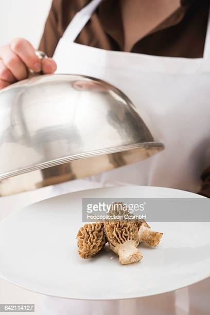 Woman serving fresh morels on plate with dome cover