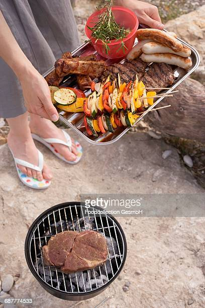 Woman serving grilled food in aluminium dish at barbecue by river