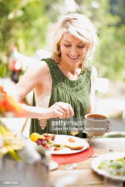 Woman serving herself at table outdoors