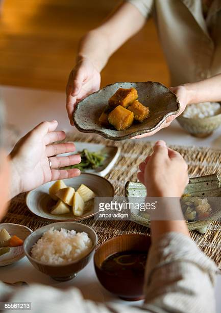 Woman serving husband food at dining table