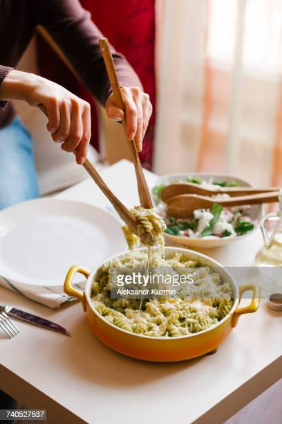 Woman serving pasta with wooden spoons