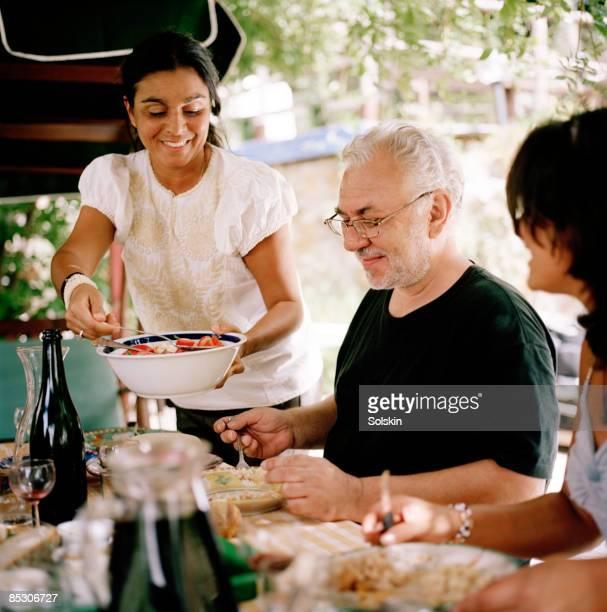 woman serving salad at garden dinner