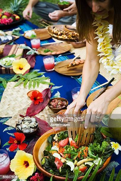 Woman serving salad at Hawaiian picnic