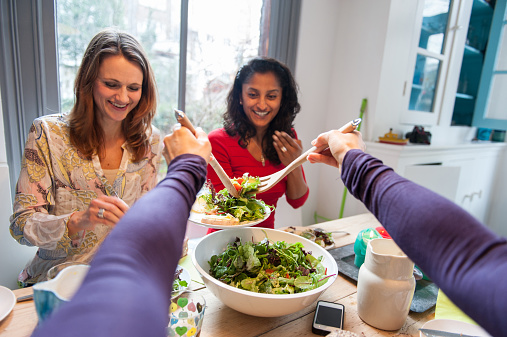 Woman serving salad from first person perspective