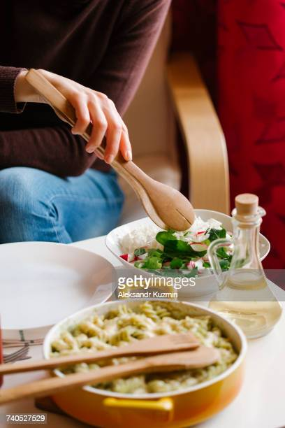 Woman serving salad with wooden tongs