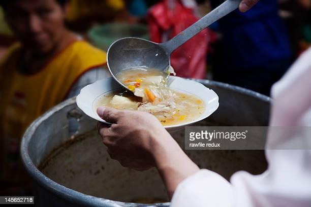 A woman serving soup at a market