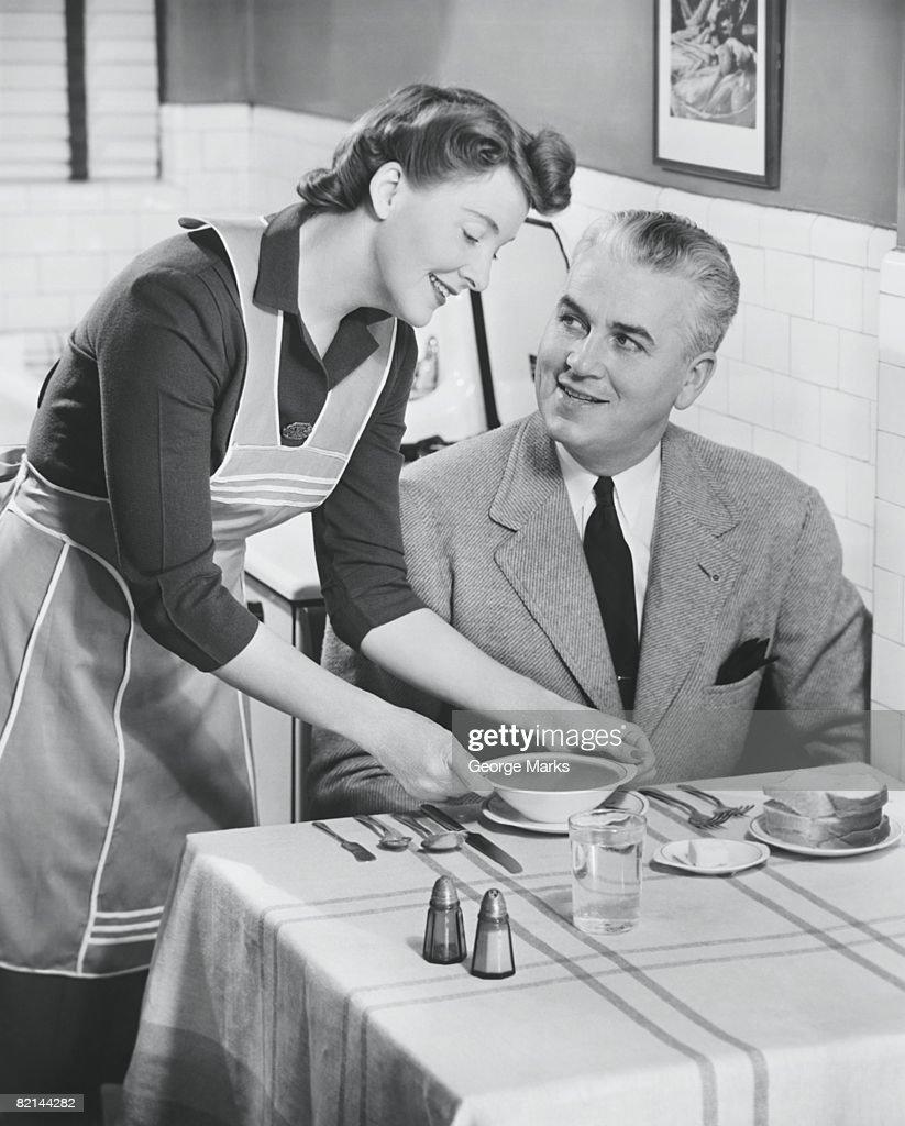 Woman serving soup to husband, (B&W) : Stock Photo