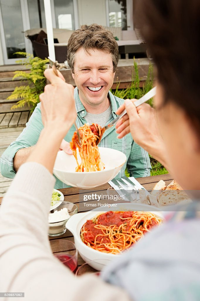 Woman serving spaghetti to man : Stock Photo