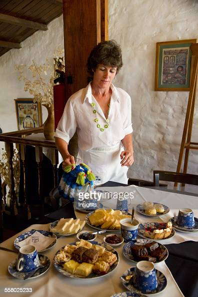 Woman Serving Tea Along With Scones Pastries Breads And Jams At Ty Gwyn A Traditional Welsh Teahouse Gaiman Chubut Argentina