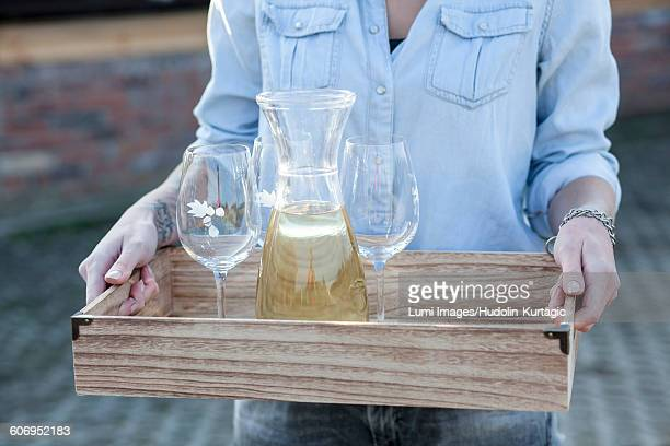 Woman serving white wine on tray