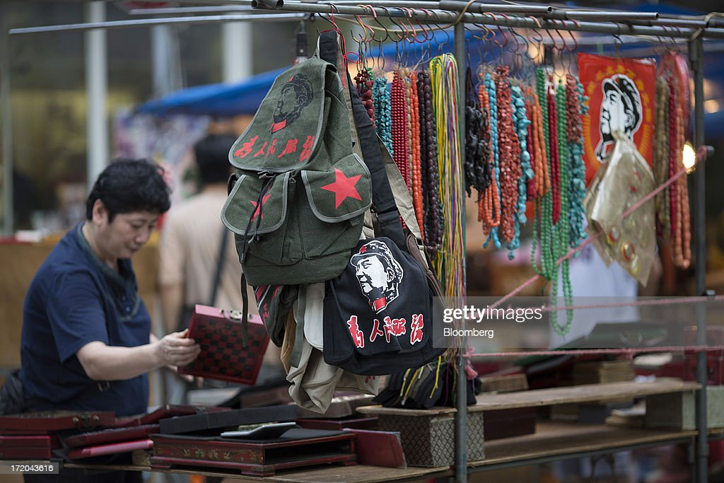 A woman sets up a market stall in the Yau Ma Tei district of Hong Kong, China, on Saturday, June 29, 2013. Hong Kongs best-selling newspapers called on readers to join a march to mark the anniversary of the citys handover to China, saying the government has failed to address issues of poverty and universal suffrage. Photographer: Jerome Favre/Bloomberg via Getty Images