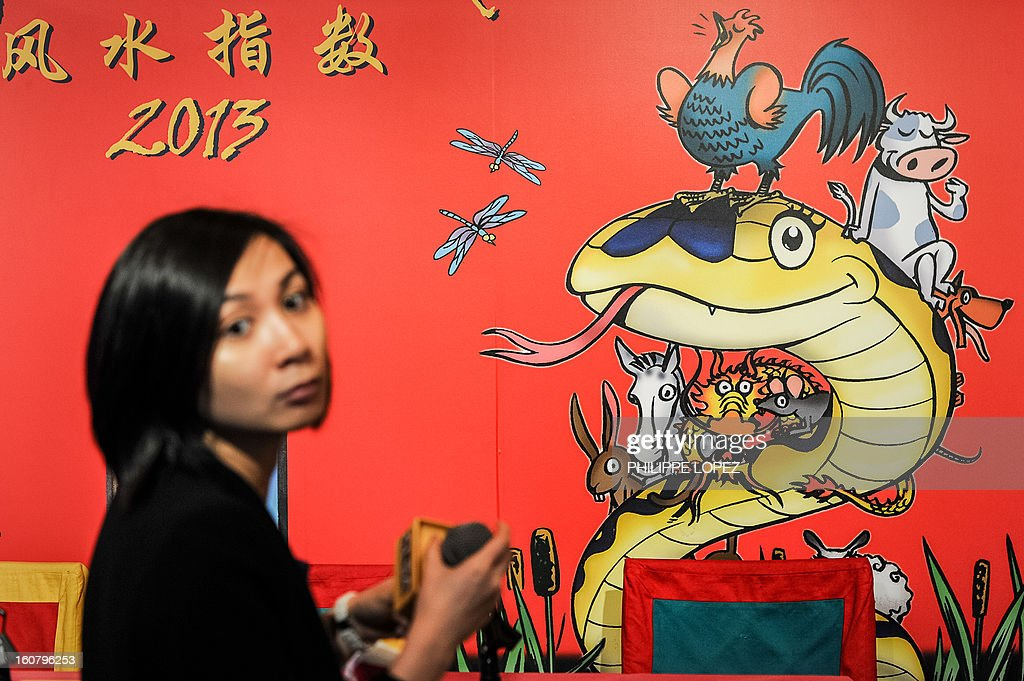 A woman sets up a microphone before the unveiling of the CLSA Feng Shui Index 2013, an annual tongue-in-cheek prediction on financial markets and world affairs, at a press conference in Hong Kong on February 6, 2013. Astrologers say the snake that will be roaming this year is identified with the element of water -- which symbolises fear -- that sits on top of the fire element, which represents joy and optimism. AFP PHOTO / Philippe Lopez