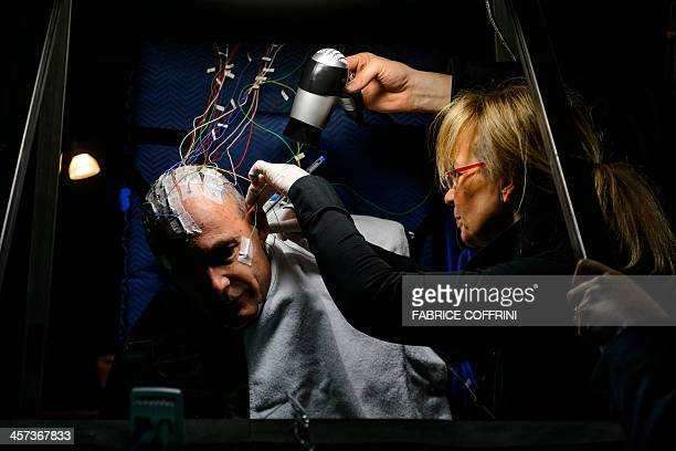 A woman sets up electrodes on the head of Swiss scientistadventurer and pilot Bertrand Piccard prior to a nonstop 72 hours simulation test flight...