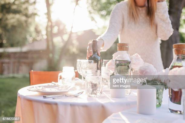 Woman setting a table in a garden, candles and a vase with pink roses.