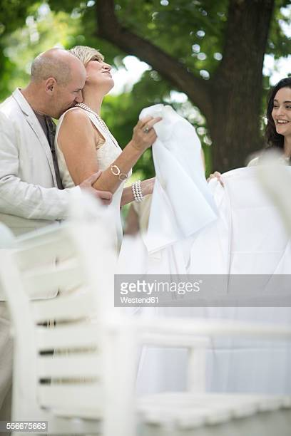 Woman setting a table outside with husband surprising her with a kiss
