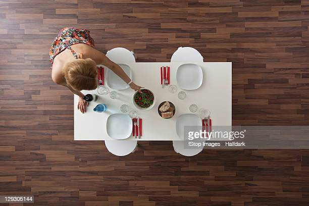 Woman setting dining room table for dinner party, overhead view