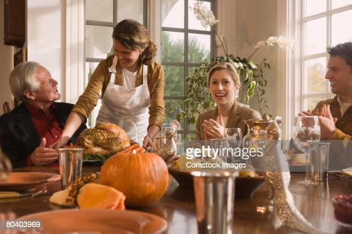 Woman setting down Thanksgiving turkey for family at dinner