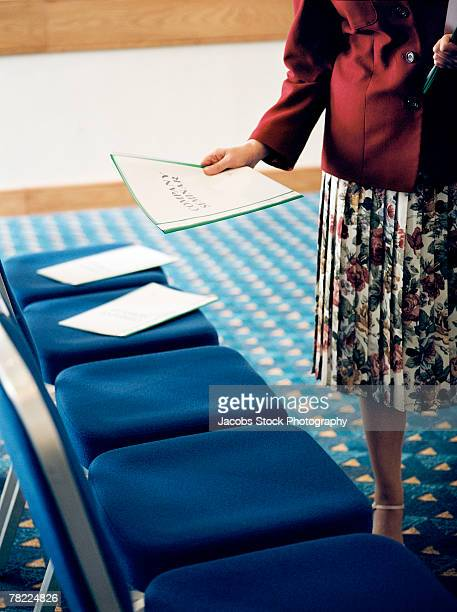 Woman setting up booklets for company seminar