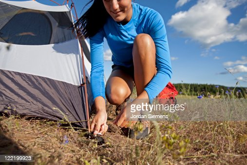 A woman setting up camp. : Photo