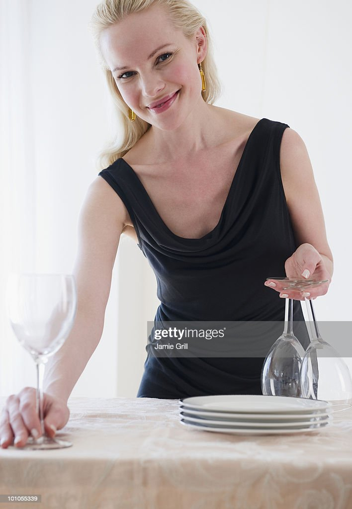 Woman setting wine glasses on dinner table : Stock Photo