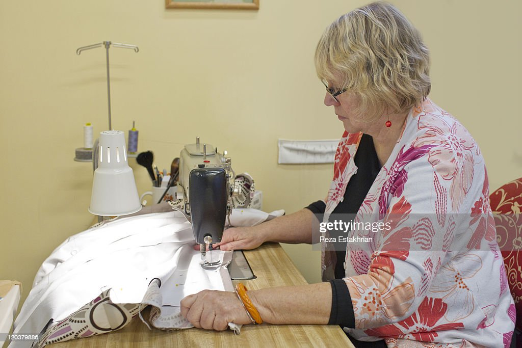 Woman sewing a curtain : Stock Photo