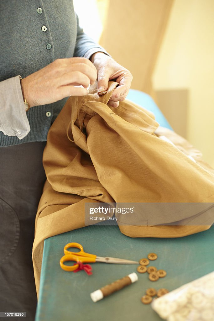 Woman sewing button on garment : Stock Photo