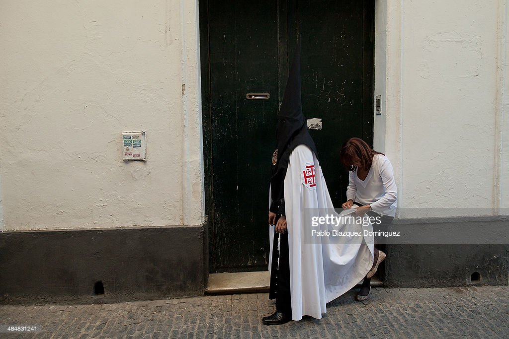 A woman sews the cape of a penitent from 'El Museo' brotherhood before he starts a procession on April 14, 2014 in Seville, Spain. Easter week is traditionally celebrated with processions in most Spanish towns.