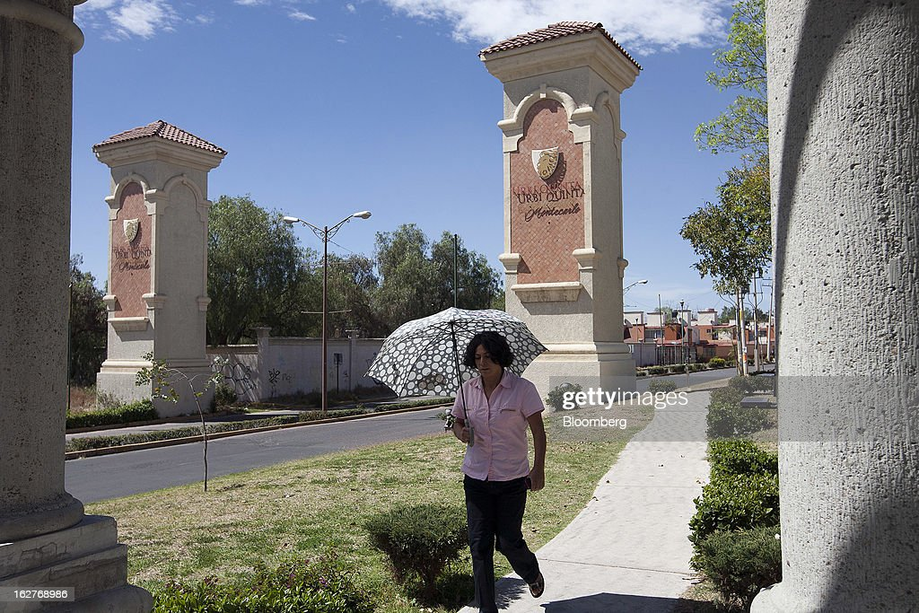 A woman shades herself with an umbrella as she walks outside the Urbi Desarrollos Urbanos SAB's Urbi Quinta Montecarlo housing development in Cuautitlan Izcalli, Mexico, on Monday, Feb. 25, 2013. Urbi Desarrollos Urbanos SAB, the Mexican homebuilder that lost three-fourths of its market value in the past year, will report negative free cash flow to equity for the fourth quarter of 2012, according to a company official with direct knowledge of the matter. Photographer: Susana Gonzalez/Bloomberg via Getty Images
