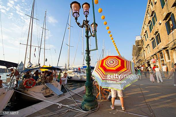 A woman shades under a big umbrella while people gather on boats of all sizes in St Mark's basin for the Redentore Celebrations on July 20 2013 in...
