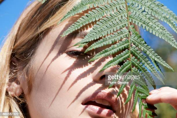 Woman shading face with fern leaf