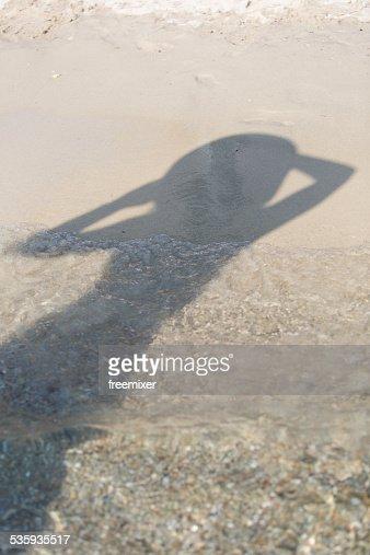 Woman shadow on a sandy beach : Stock Photo