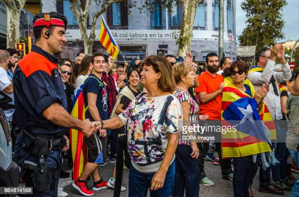 A woman shakes hand with a catalan local police in gratitude for his work About 450000 people have been focused to support the Government and the...
