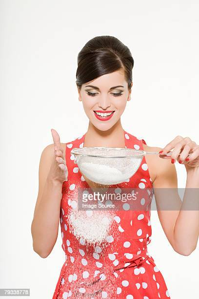 Woman shaking flour from a sieve