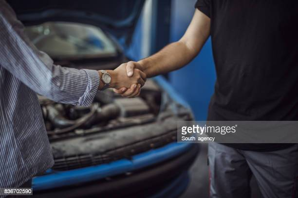 Woman Shaking Hands With Car Mechanic
