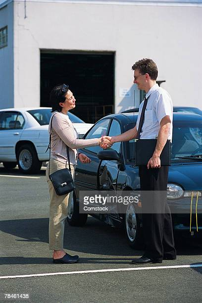 Woman shaking hands with car salesman or insurance agent