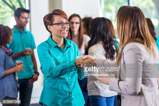 Woman shaking hands with colleague during mixer or party