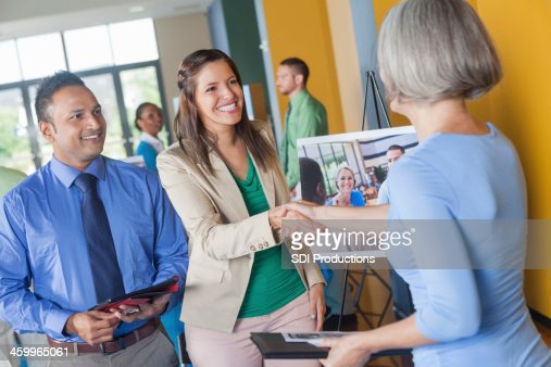 Woman shaking hands with professional executive at job fair event