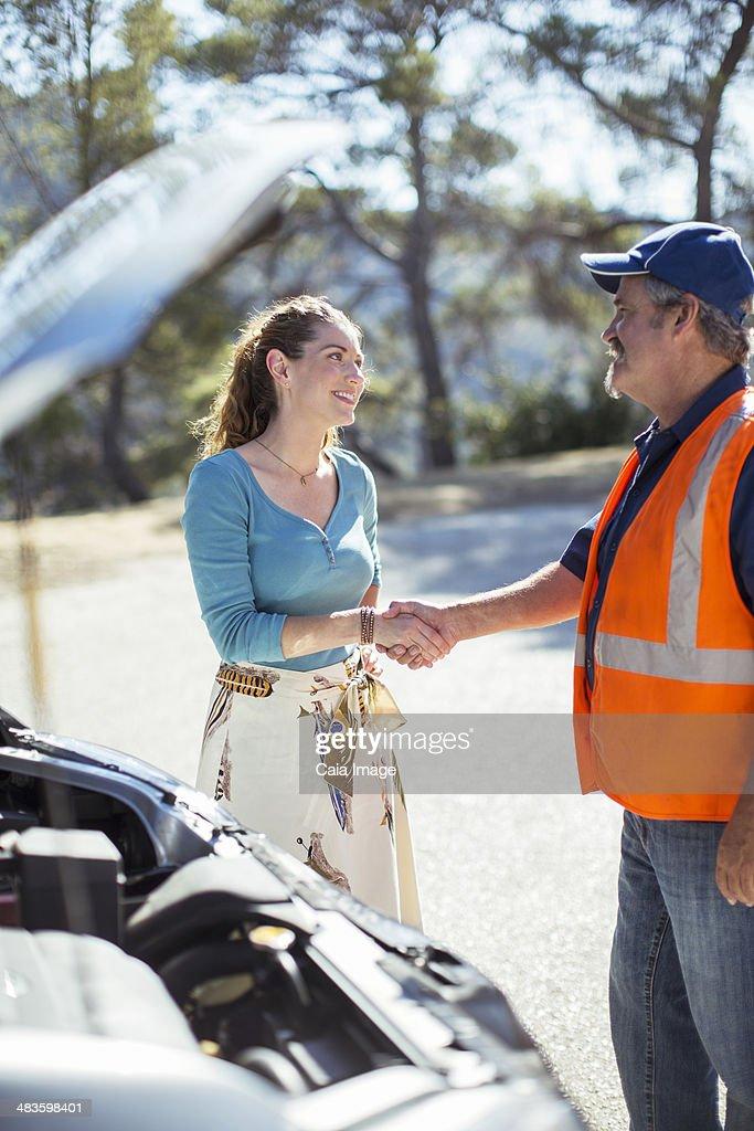 Woman shaking hands with roadside mechanic