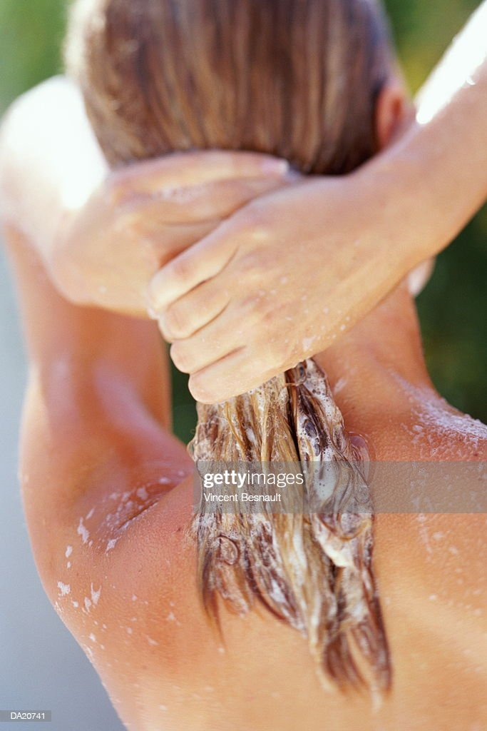 Woman shampooing hair, close-up, rear view : Stock Photo