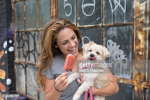 Woman sharing popsicle with morkie dog : Stock Photo