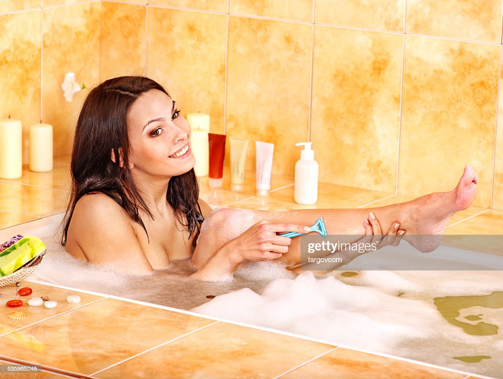 Woman shaving her legs in  bath : Stock Photo