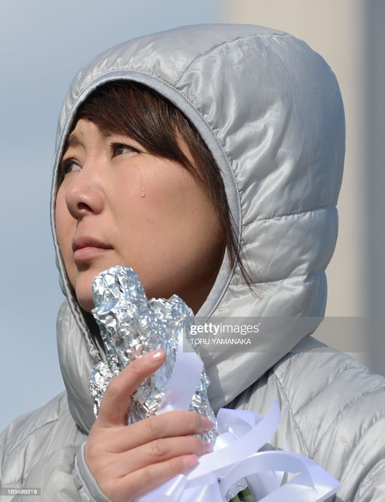 A woman sheds tears for tsunami victims in Arahama district in Sendai, Miyagi Prefecture on March 11, 2013. Japan on March 11 marked the second anniversary of a ferocious tsunami that claimed nearly 19,000 lives and sparked the worst nuclear accident in a generation. AFP PHOTO/Toru YAMANAKA