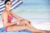 Woman Sheltering From Sun Under Beach Umbrella Putting On Sun Cream