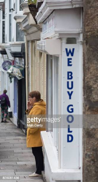 A woman shelters from the rain in Redruth on July 26 2017 in Cornwall England Figures released by Eurostat in 2014 named the British county of...