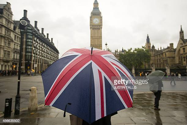 A woman shelters from the rain under an umbrella in front of the Houses of Parliament in central London on 4 October 2014 AFP PHOTO / JUSTIN TALLIS