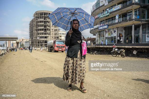 A woman shelters from the sun with an umbrella as she walks along the construction site of Asmara road on July 02 2014 in Addis Ababa Ethiopia The...