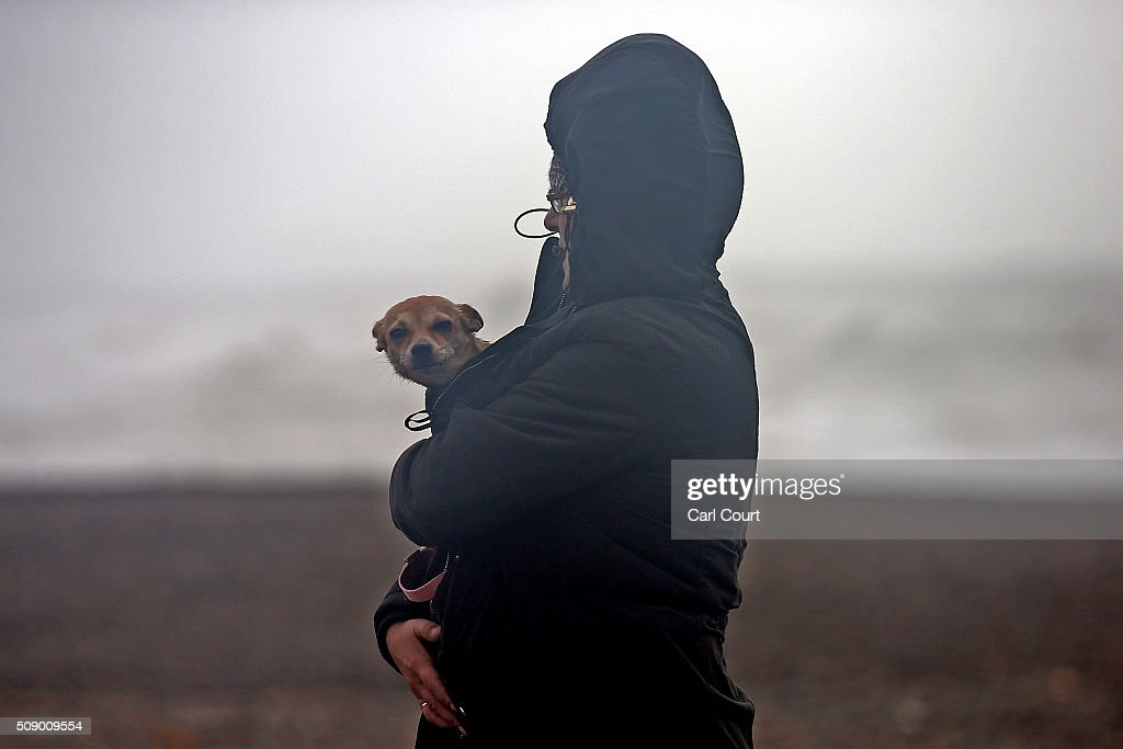 A woman shelters her small dog as she walks along a beach on February 8, 2016 in Newhaven, East Sussex. Storm Imogen is the ninth named storm to hit the UK this season. This year's storms are being named in an effort by the Met Office and Met Eireann to increase public awareness and safety. They were named by public ballot and there are no names for the letters Q, U, X, Y and Z.