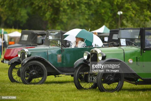 A woman shelters under an umberella in her Austin Seven Tourer 'Chummy' at the 50th Austin Seven rally at the National Motor Museum in Beaulieu...
