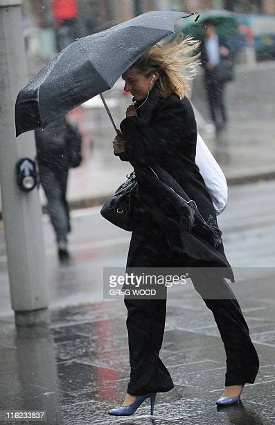 A woman shelters under an umbrella as she struggles to walk into the wind at Circular Quay in Sydney on June 15 2011 Damaging winds and heavy rain...