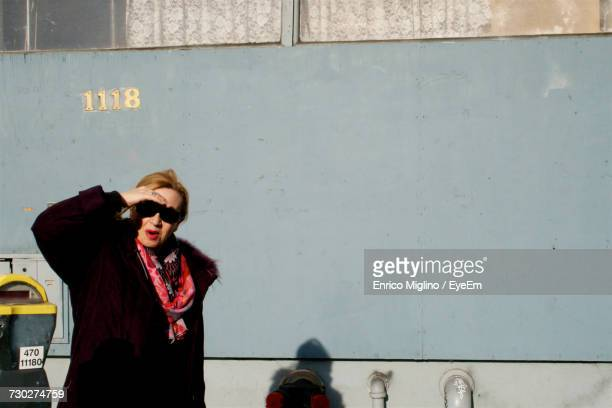 Woman Shielding Eyes While Standing By Wall